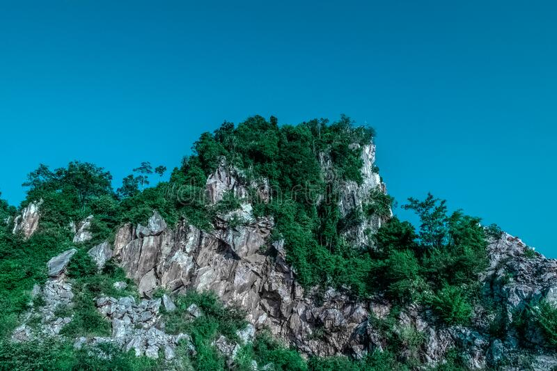 Tree covered rocky crag stock images