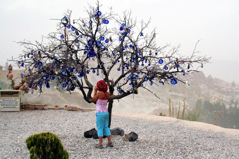 Tree decorated with Evil Eyes, in the valley of Uchisar in Cappadocia , Turkey. UCHISAR - TURKEY ON 08/06/2016 - young girl hanging evil eye on a tree in the royalty free stock image