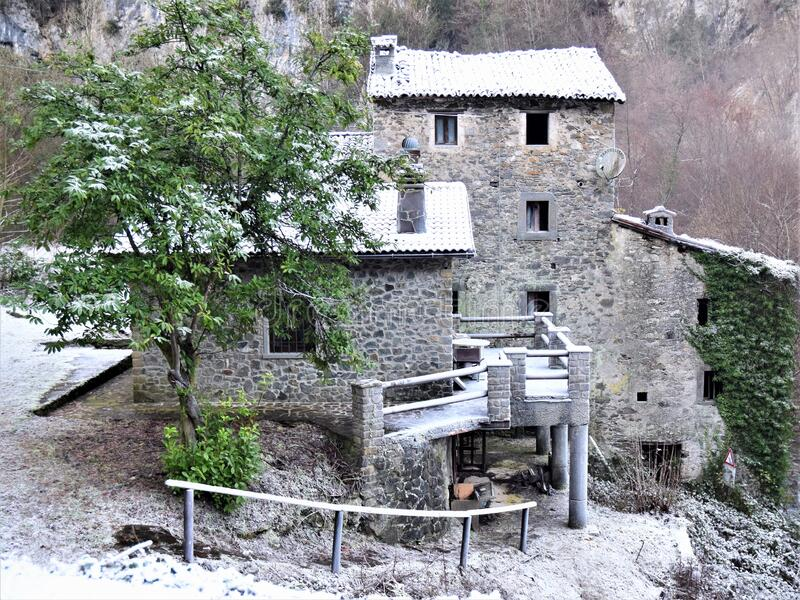 Tree in front of a stone house with a roof covered with frost on the mountainside, along the trada that leads to the lake of Isola. Santa, magic in the heart of stock image