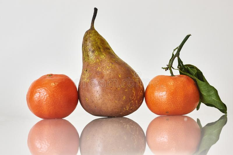 Tree fruits on white background, pear and oranges royalty free stock images