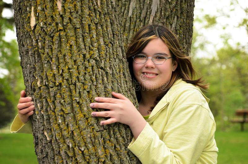 Tree Hugger. A smiling young girl is hugging a tree royalty free stock photo