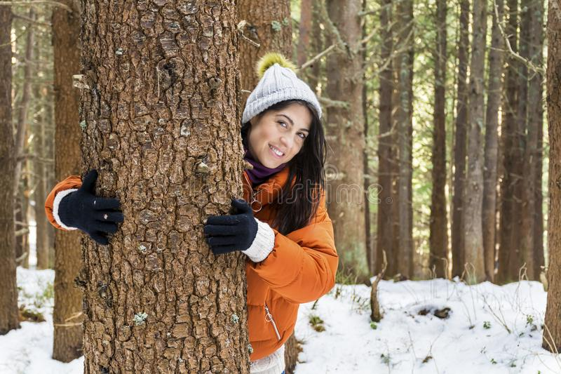 Woman hugging a tree in the winter forest .loving nature. Tree hugger.smiling woman woman hugging a tree in the winter forest royalty free stock photography