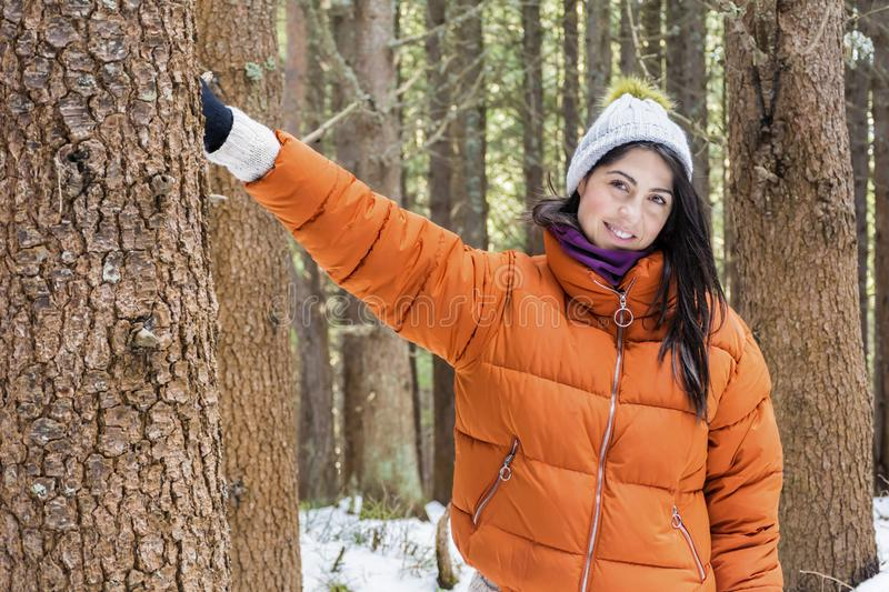 Woman in the winter forest .loving nature. Tree hugger.smiling woman woman hugging a tree in the winter forest stock photo