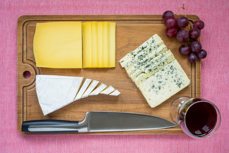Tree kind of sliced cheese, glass of red wine, sweet red grapes and chef knife on brown wooden cutting board. cheese with edible royalty free stock photography