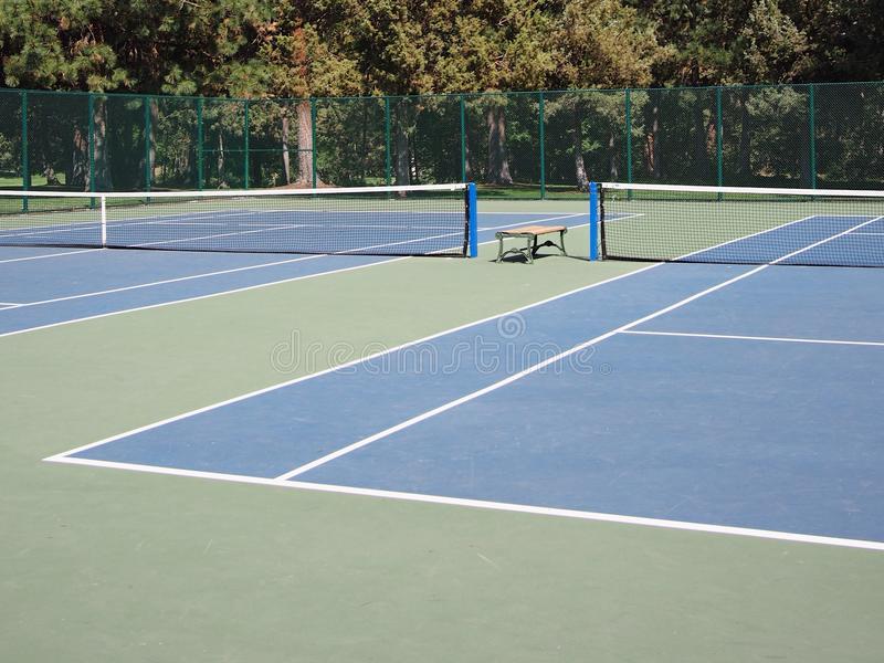 Blue courts. Tree lined blue tennis courts in an urban park stock photos