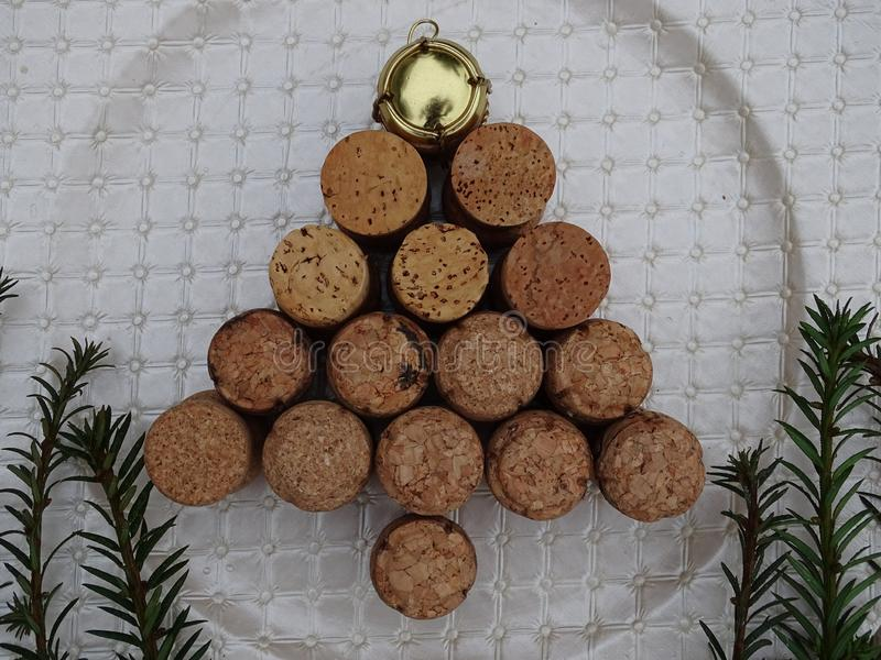 Tree made of cork stoppers on plate. And green plants golden top royalty free stock image
