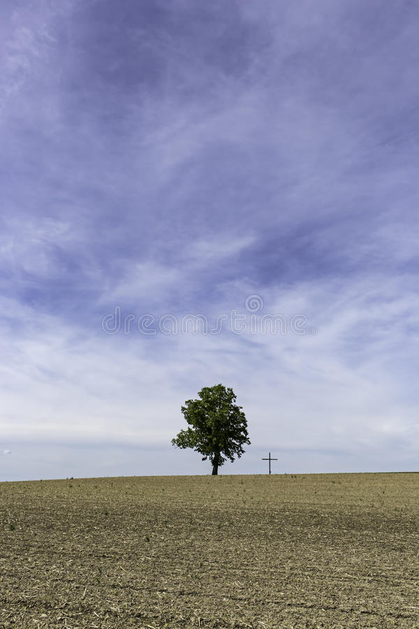 Tree next to cross below huge blue sky. The silhouette of beautiful single tree next to a cross, the symbol of Christianity royalty free stock photo