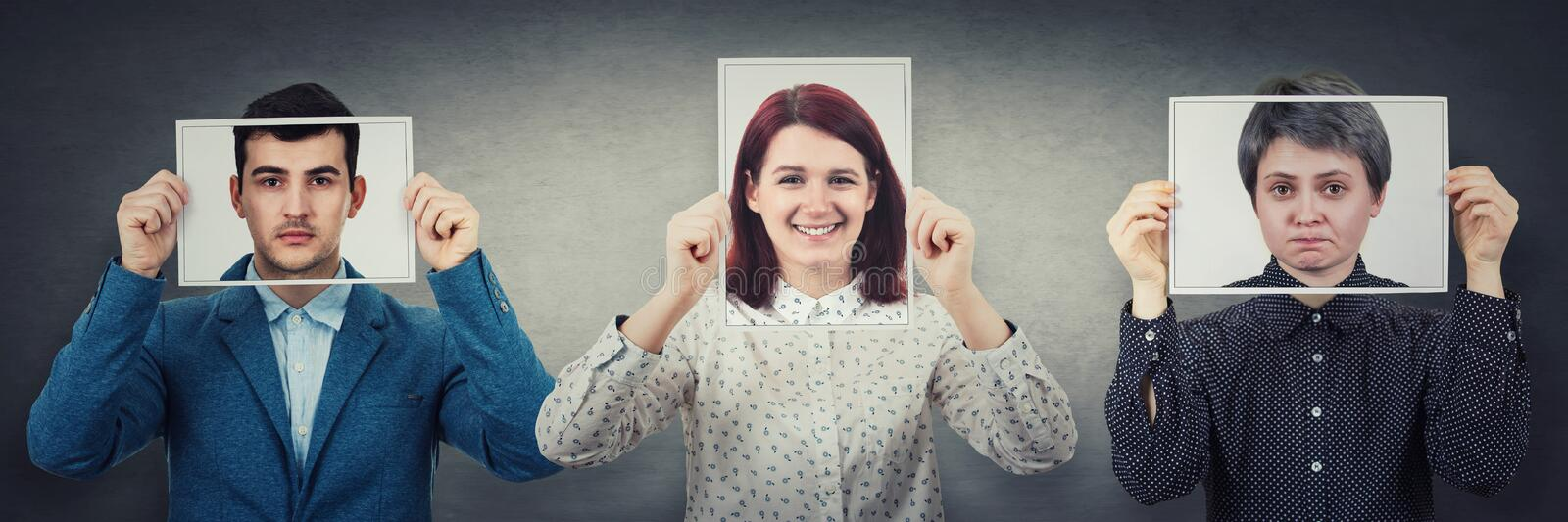 Tree people covering their faces using photo sheets with happy, sad and neutral emotions, like mask to hide real expression from royalty free stock photo