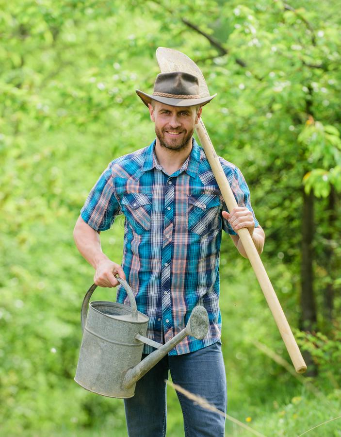 Tree planting tradition. Growing plants. Mature guy cowboy hat with watering can and shovel. Arbor day. Planting trees. Commitment and responsibilities royalty free stock photos
