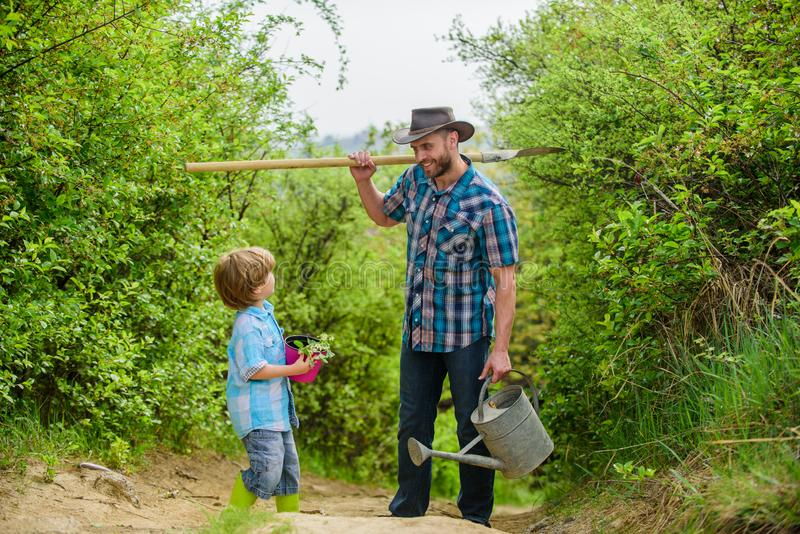 Tree planting tradition. Little helper in garden. Planting flowers. Growing plants. Boy and father in nature with. Watering can and shovel. Dad teaching son stock photography