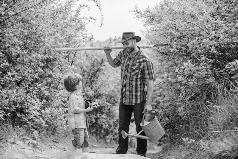 Tree planting tradition. Little helper in garden. Planting flowers. Growing plants. Boy and father in nature with. Watering can and shovel. Dad teaching son royalty free stock photo