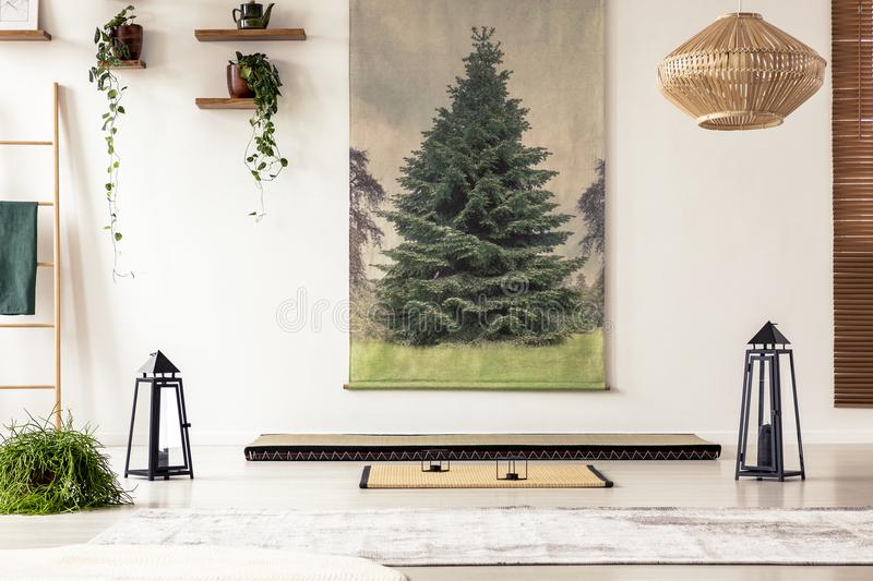 Tree poster on the wall, lamps, plants, tatami mat and mattress. In a Japanese room interior royalty free stock photography