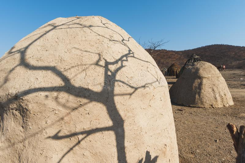 Himba tribe village. Tree shadow on traditional hut made from dry grass and clay in Himba tribe village in Namibia royalty free stock image