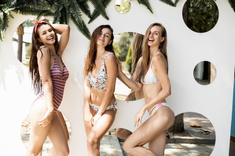 Tree slender beautiful girls in a swimsuits are posing against the wall with round mirrors on the open air on a sunny. Summer day royalty free stock photography