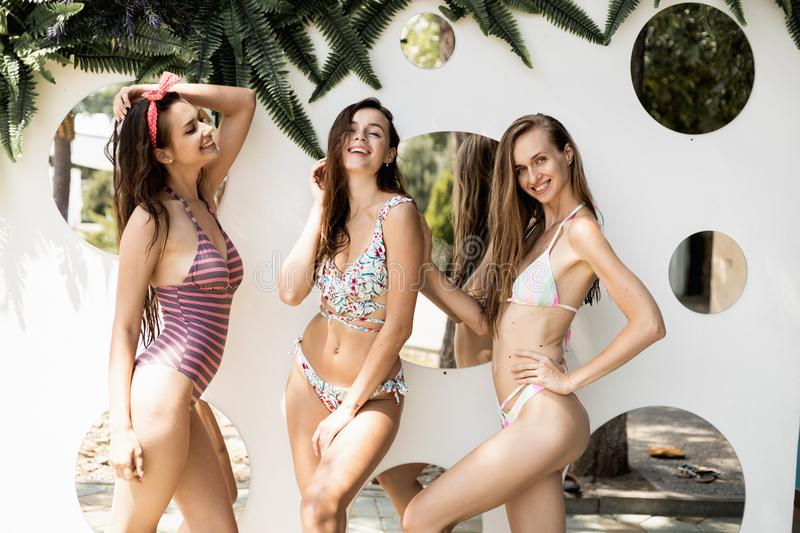 Tree slender beautiful girls in a swimsuits are posing against the wall with round mirrors on the open air on a sunny. Summer day stock image