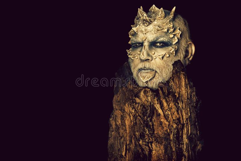 Tree spirit and fantasy concept. Monster with sharp thorns and warts. Druid behind old bark isolated on black. Goblin with horns on head. Man with dragon skin stock photos
