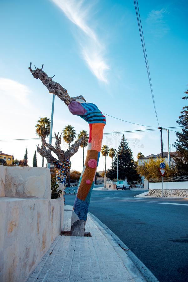 Tree with storm yarn. Artistic and creative street art. Colored. Wool in the trees. Street landscape stock photography