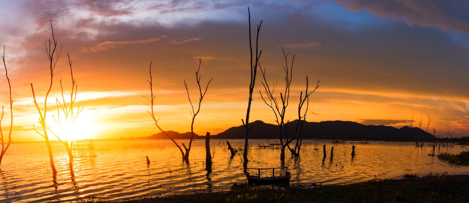 The tree , sun, cloud and water to be landscape. the mountain are background the lake. stock photos