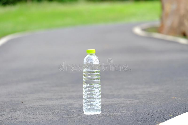 A plastic bottle of drinking water on the pavement lane at the park stock photography