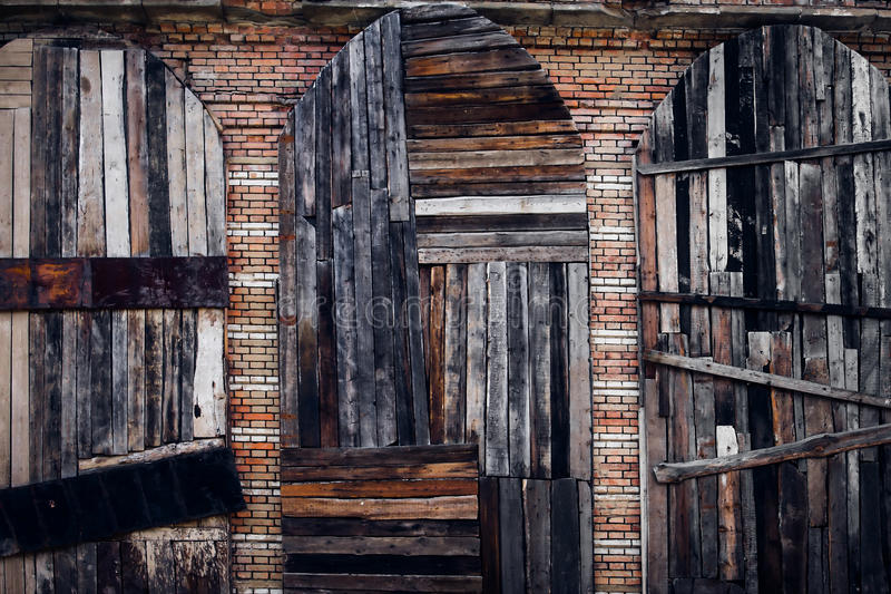 Tree wooden doors. Three vintage doors from the old boards on a brick wall background royalty free stock image