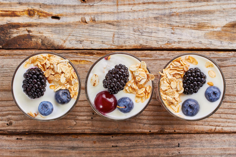 Tree yogurt desserts with berries and muesli in row. royalty free stock photography