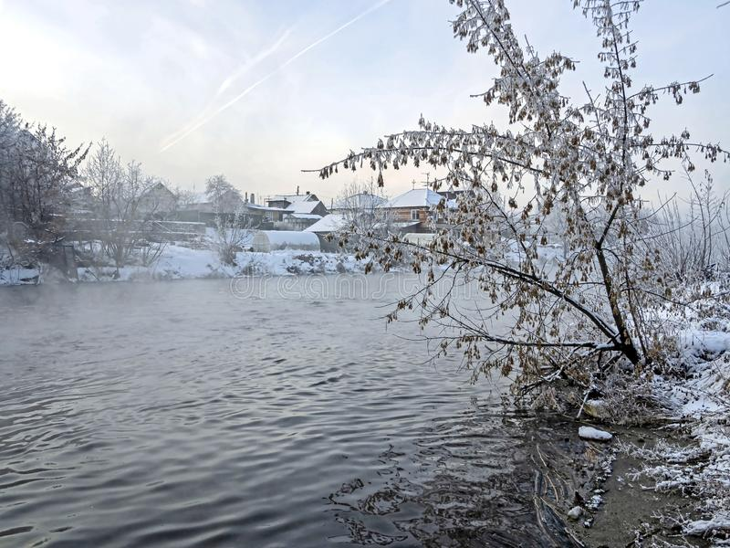 Trees covered with frost near the unfrozen river in winter. On the Bank of the unfrozen river trees covered with frost in winter in the southern Urals, the fog stock images