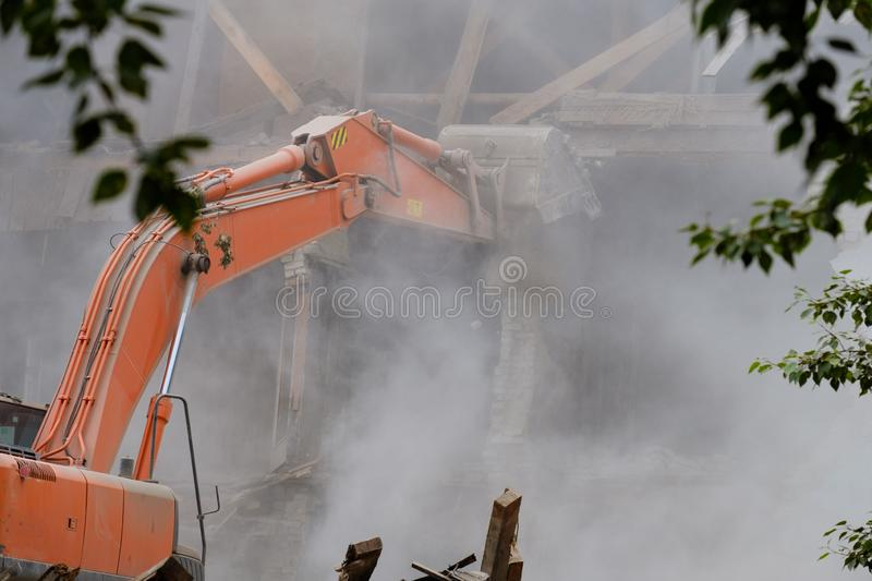 Through the trees on the foreground is an excavator bucket to break the building, dismantling of damaged buildings, dust and stone. S. destruction of buildings stock photos