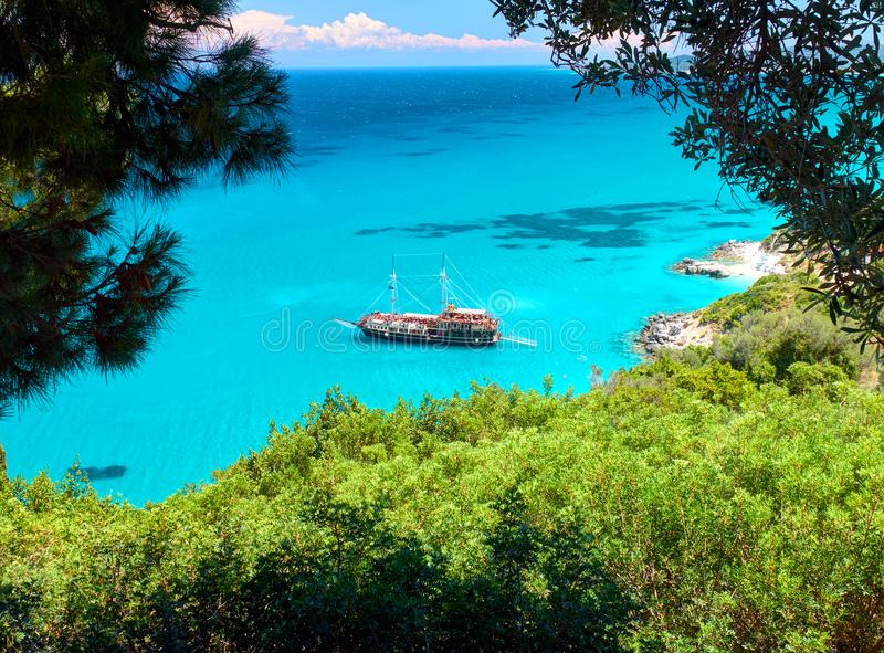 Trees frame beautiful view on amazing island bay with pirate corsair style boat ship, swimming people, beach in Ionian Sea blue wa stock photography