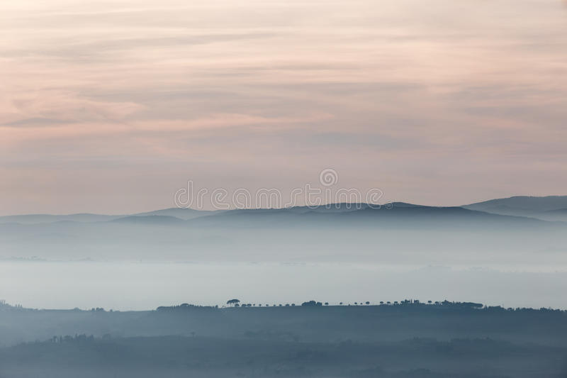 Trees, hills and fog royalty free stock photo