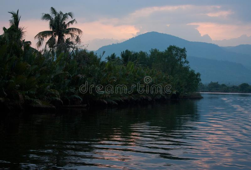 Trees and mountains during a beautiful sunset near Kampot in Cambodia. In Asia, adventure, asian, boat, calm, chhu, chill, cloud, color, cruise, dark stock photography