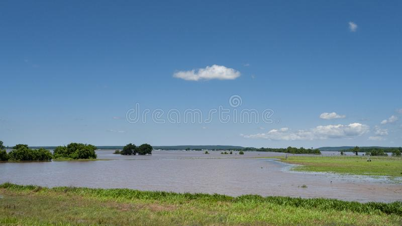 Farmland under water during spring flooding. Trees are in standing water, farm buildings in the far distance with water in the field during spring flooding stock images