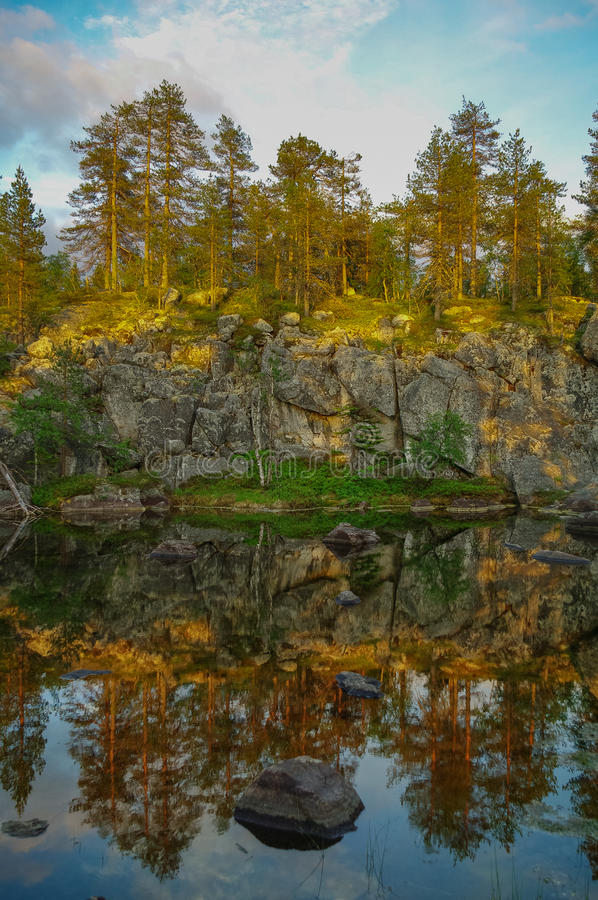 Trees and stones reflection on little lake on mountain Vottovaara, Karelia, Russia stock images