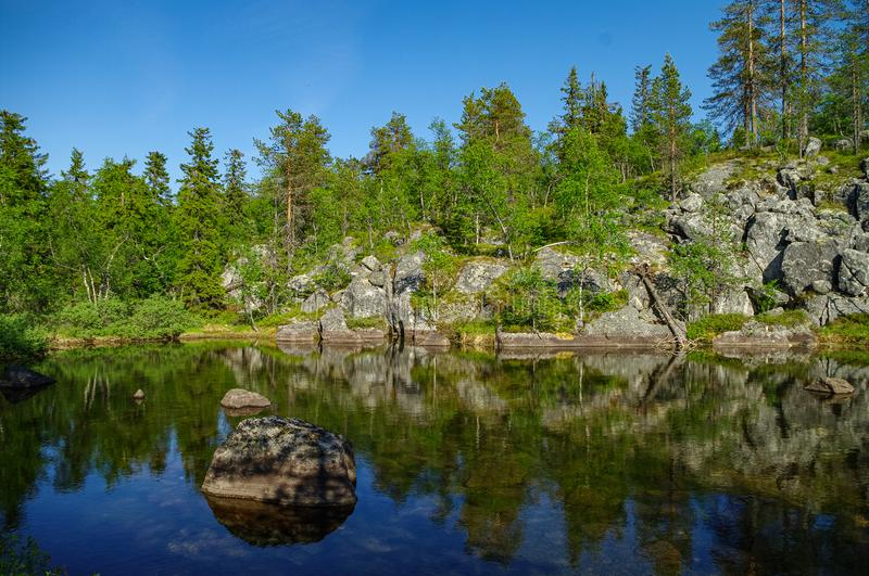 Trees and stones reflection on little lake on mountain Vottovaara, Karelia, Russia.  royalty free stock photo