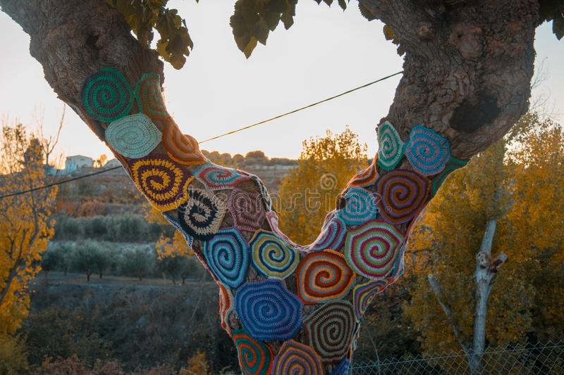 Trees with storm yarn. Decorated with coloured wool. Street Art. Hippie concept royalty free stock photos