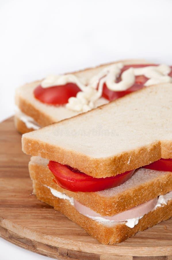 Trefaldig smörgås med salamitomaten och gräddfil arkivfoton