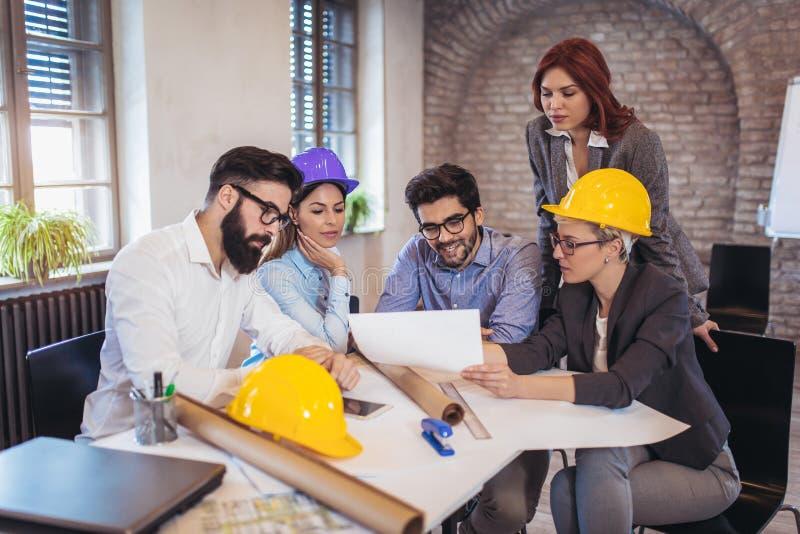Treffen des Teams der Ingenieure, die an einem Bauvorhaben arbeiten lizenzfreie stockfotos