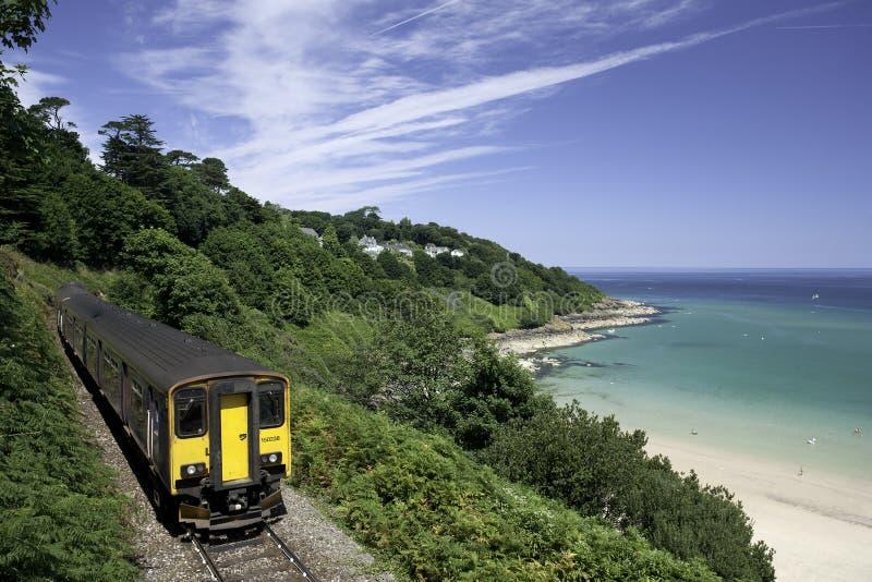 Trein aan het strand het UK stock afbeeldingen