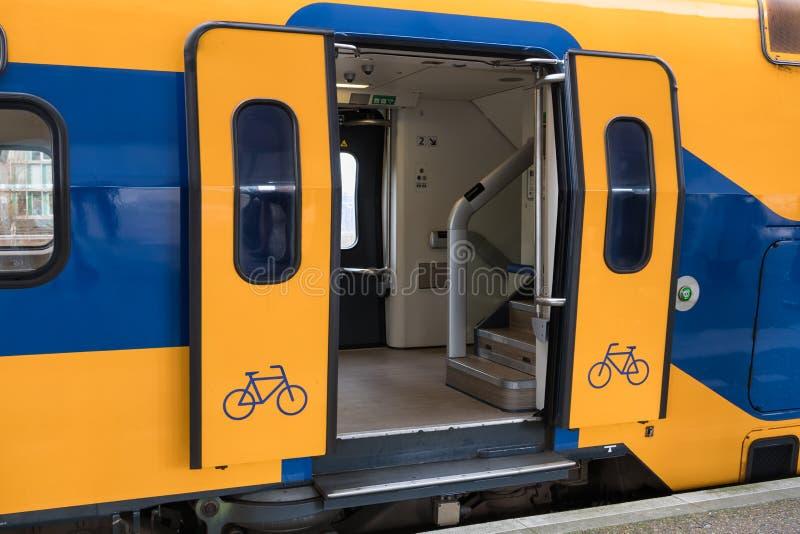 Trein bij Nederlands spoorwegplatform met open deur stock foto's