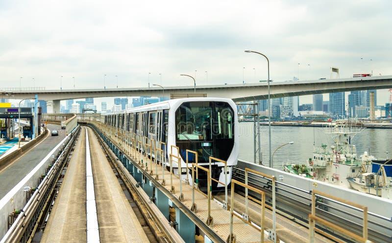 Trein bij Yurikamome-lijn, een geautomatiseerd systeem van de leibaandoorgang in Tokyo stock afbeelding