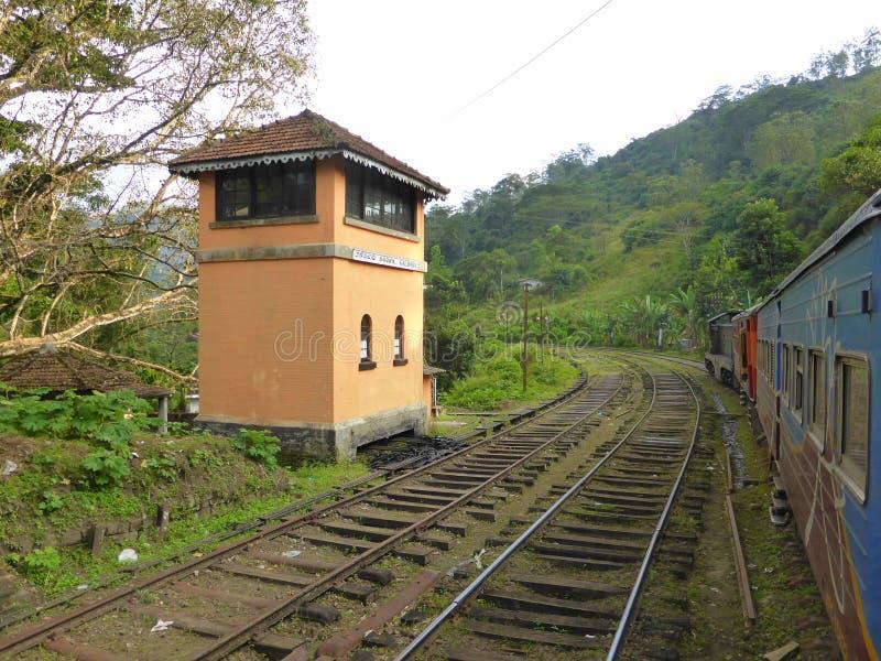 Trein die een spoorwegseinhuisje overgaan stock foto's