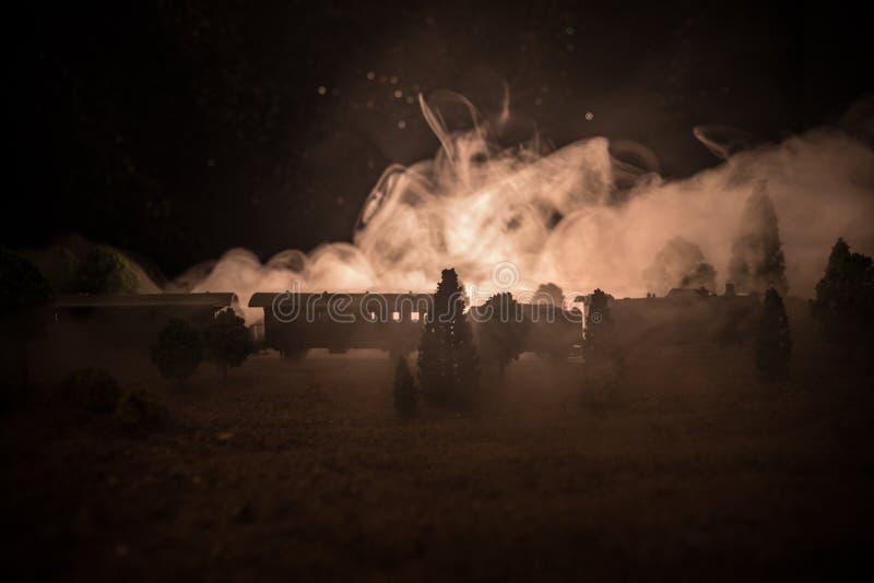 Trein die zich in mist bewegen Oude stoomlocomotief in nacht Nachttrein die zich op spoorweg bewegen gestemde mistige brandachter royalty-vrije stock afbeeldingen