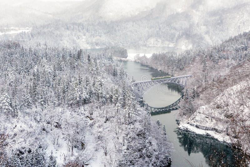 Trein op de brug over Tadami-rivier in Japan royalty-vrije stock afbeeldingen