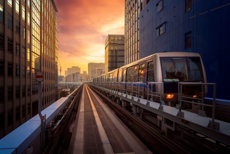 Trein in stad in Tokyo met zonsondergangachtergrond royalty-vrije stock fotografie