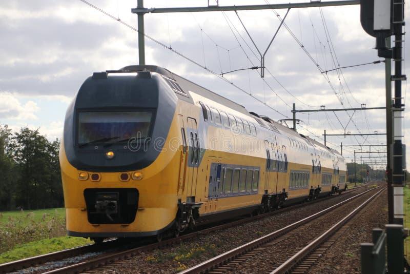 Trein typeDD VIRM van NS die bij het spoorwegspoor lopen in het hol IJssel van Nieuwerkerk aan in Nederland royalty-vrije stock fotografie