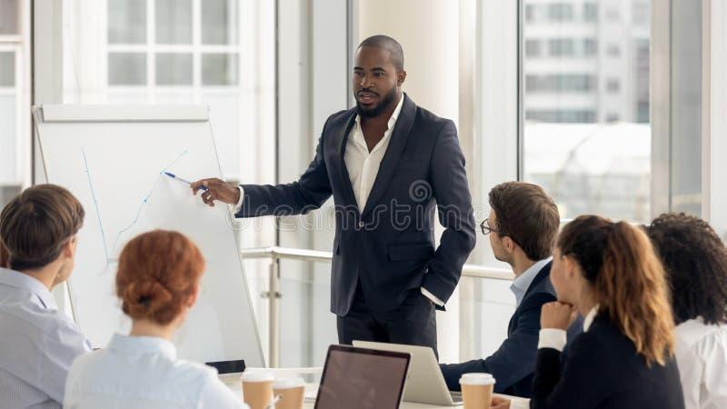 Treinador afro-americano que fala à audiência que dá a apresentação no flipchart fotos de stock