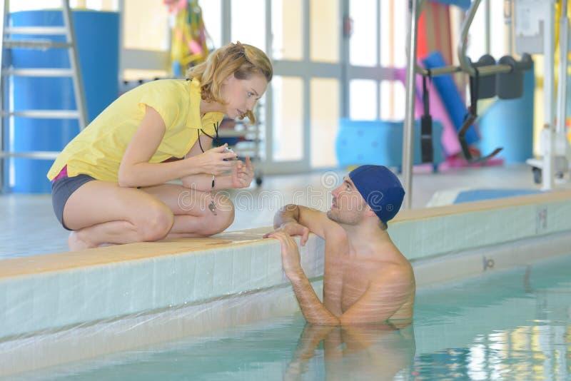 Treinador com o cronômetro na piscina imagens de stock royalty free