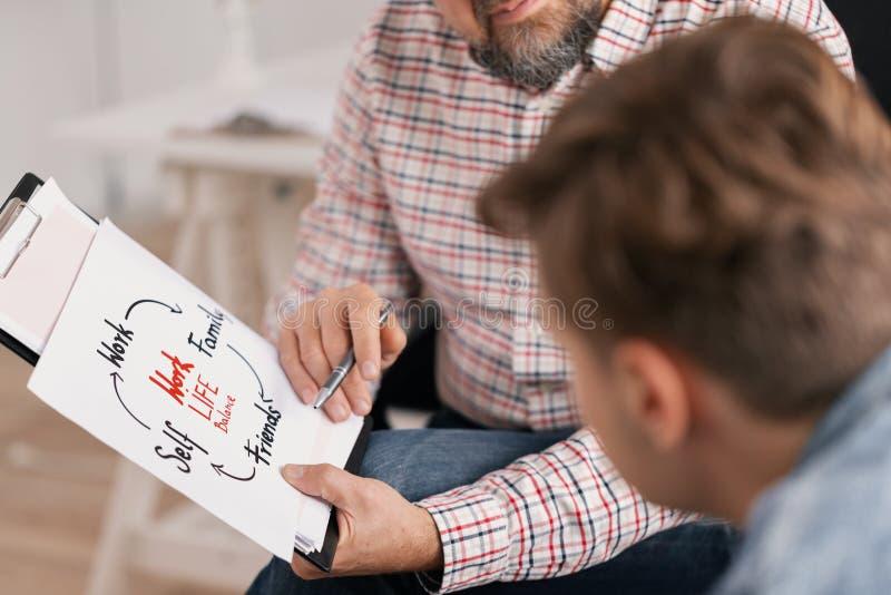 Treinador da vida pessoal que explica o gráfico a seu paciente novo fotografia de stock