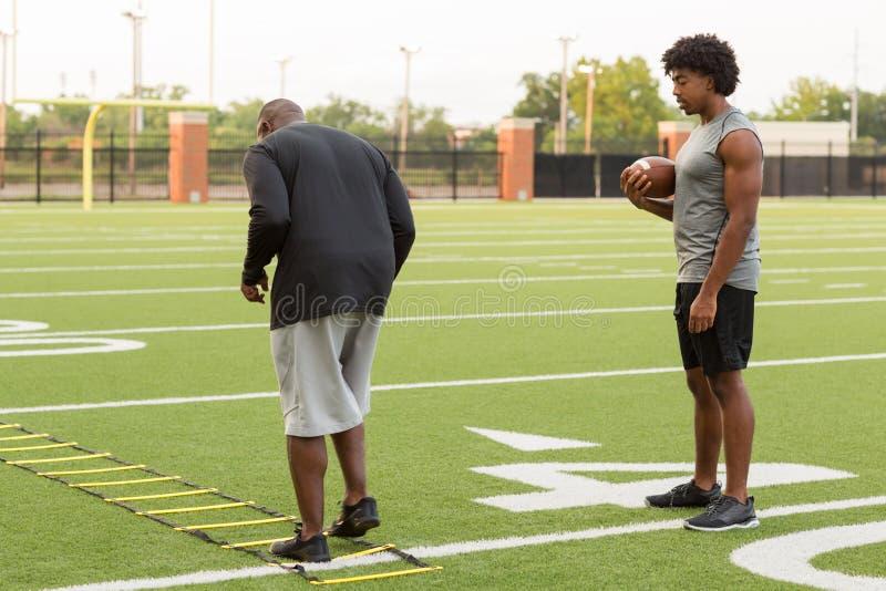 Treinador de futebol americano que treina um atleta novo fotografia de stock royalty free