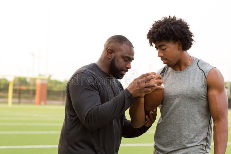 Treinador de futebol americano que treina um atleta novo foto de stock royalty free