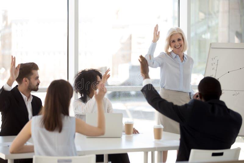 Treinador de sorriso que levanta a mão com a equipe diversa que contrata na votação imagem de stock royalty free